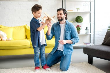 happy father and cute little son playing with wooden toy plane at home