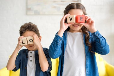 adorable little children holding wooden cubes with word love