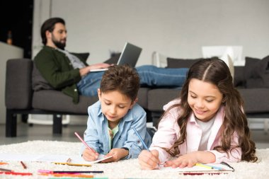 cute smiling kids lying on carpet and drawing with colored pencils while father using laptop on sofa behind