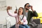 Fotografie Šťastný otec a dcera předstírá, Piráti a pořizování selfie s smartphone doma