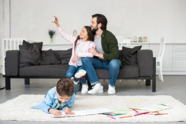 happy father and daughter sitting on sofa and taking selfie with smartphone while little boy drawing on carpet at home