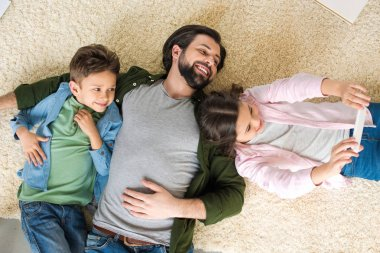 top view of father with two adorable kids lying on carpet and taking selfie with smartphone