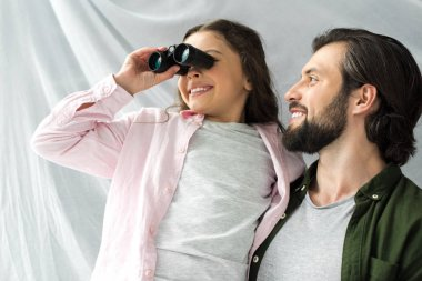 happy father and daughter having fun together and playing with binoculars