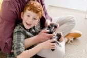 Fényképek vágott lövés apja és boldog kis fia játszik botkormány otthon