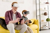 Fotografie happy father and son in virtual reality headsets playing with joysticks at home