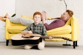 Photo cute little boy holding acoustic guitar ad smiling at camera while father using digital tablet on sofa behind