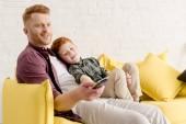 Fényképek boldog apa és fia együtt ül a kanapén, és használ távoli ellenőr otthon tévénézés közben