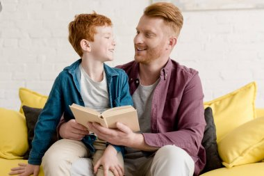 happy father and son smiling each other while reading book together at home