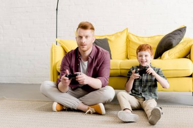 happy father and son sitting on carpet and playing with joysticks at home