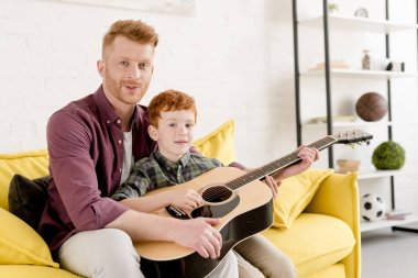 happy father and son holding acoustic guitar and smiling at camera at home