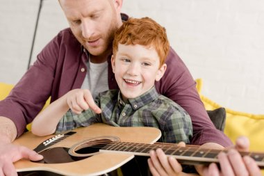 cropped shot of father teaching happy son playing guitar at home