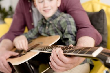 close-up view of father teaching little son playing acoustic guitar