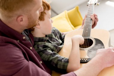 cropped shot of father teaching little son playing acoustic guitar