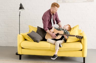 happy redhead father and son playing acoustic guitar together at home