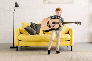 adorable happy little boy playing guitar at home