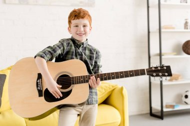 cute little boy holding acoustic guitar and smiling at camera