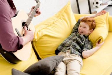 cropped shot of father playing guitar while cute happy son lying on couch