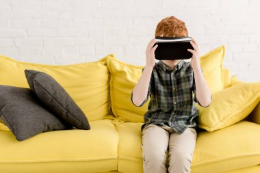 cute little boy in virtual reality headset sitting on couch