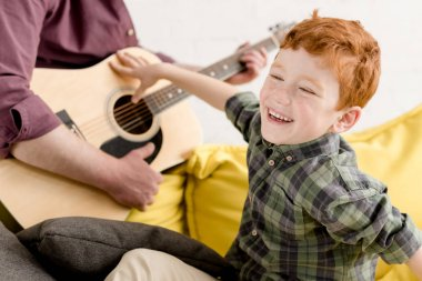 cropped shot of cute little boy laughing and father playing guitar