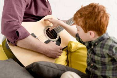 cropped shot of cute little boy looking at father playing guitar
