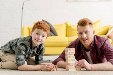 happy red haired father and son smiling at camera while playing with wooden blocks at home