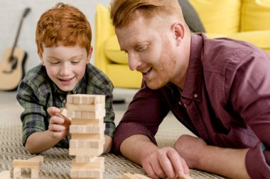 happy redhead father and son lying on carpet and playing with wooden blocks