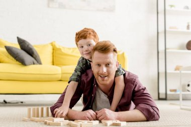 happy father and son smiling at camera while playing with wooden blocks at home