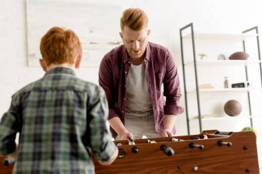 redhead father and son playing table football together at home
