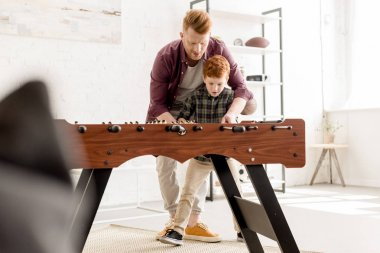 selective focus of father and son playing table football together at home