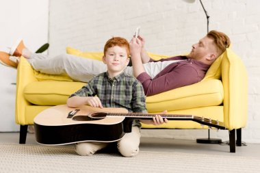 cute little boy holding acoustic guitar ad smiling at camera while father using digital tablet on sofa behind