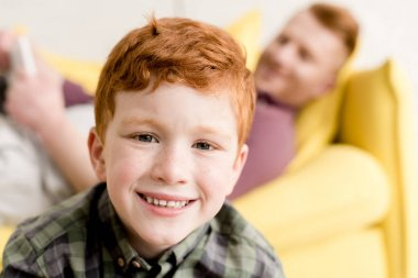 close-up view of cute redhead boy smiling at camera while spending time with father at home