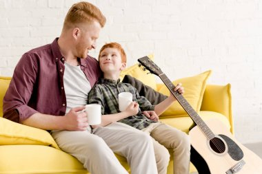 happy father and son holding mugs and acoustic guitar while sitting on couch at home
