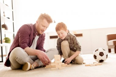 smiling father and son playing with wooden blocks at home