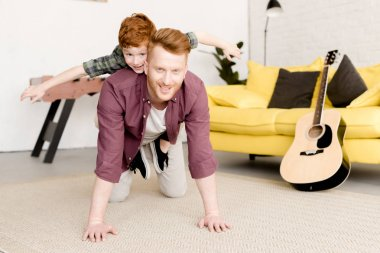 happy redhead father and son smiling at camera while having fun together at home