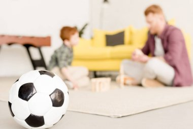 close-up view of soccer ball and father with son playing behind