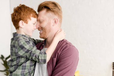 side view of happy red haired father and son hugging at home