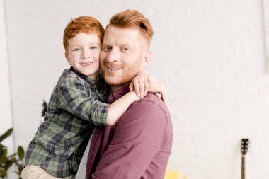 happy redhead father and son hugging and smiling at camera
