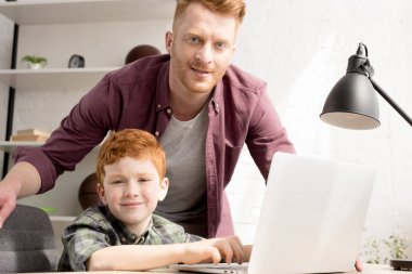 smiling father and son using laptop together and looking at camera at home