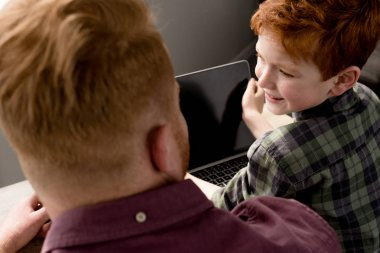 cropped shot of father and son using laptop with blank screen