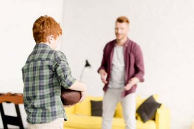 redhead father and son playing with rugby ball at home