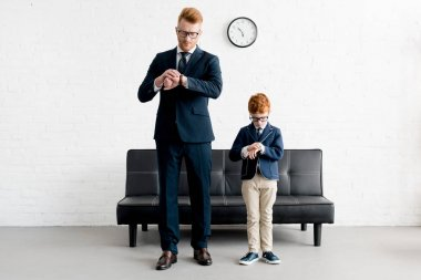 father and little son in formal wear and eyeglasses checking wristwatches together