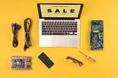 Fotografia vista del computer portatile con iscrizione cyber lunedi vendita solo un giorno, smartphone, occhiali da vista e fili su colore giallo