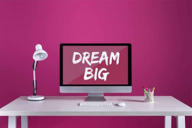 Desktop computer with dream big inscription on screen, keyboard, computer mouse and office supplies on table stock vector