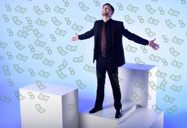 businessman in black suit with outstretched arms standing on white block with falling dollar banknotes on blue