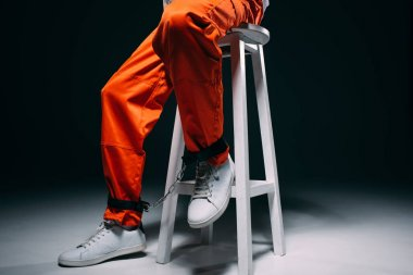 Cropped view of man in orange uniform with cuffs on legs sitting on stool on dark background