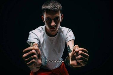 Sad man in prison uniform showing cuffs on dark background