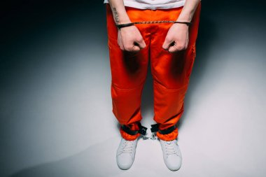 Cropped view of man wearing orange pants in cuffs on dark background