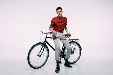 Hipster male cyclist leaning on his bike on white background stock vector