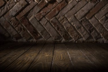 close up view of wooden tabletop and brick wall background