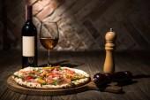 Selektivní fokus italskou pizzu, koření v brusky, láhve a sklenky vína na dřevěnou desku